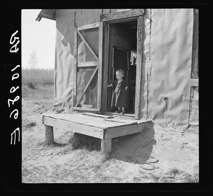 10. A young child stands in the doorway of his shack home near Long Lake, Wisconsin.
