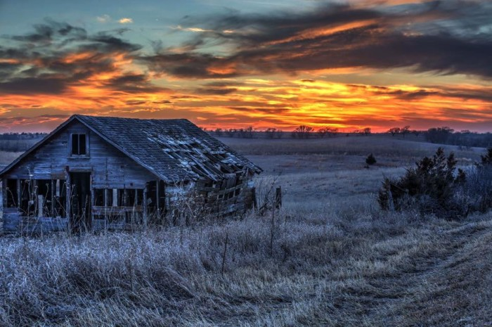 A beautiful country scene: an old barn highlighted a warm sunset.