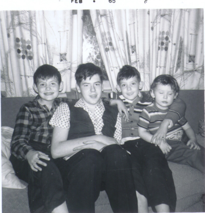Four brothers hanging out on a couch in 1965.