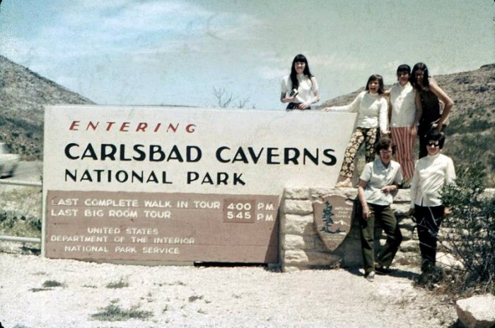 4. A group of people posing by the sign to Carlsbad Caverns.
