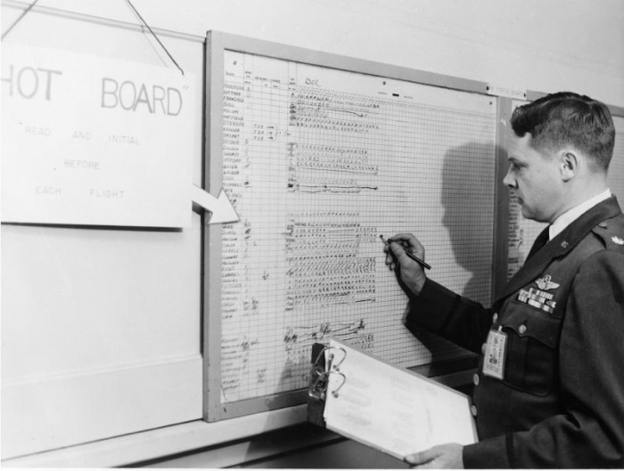 The director of training working out the scheduling board at Lincoln AFB.