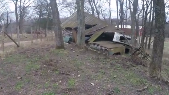 Storage shed with abandoned vehicle.