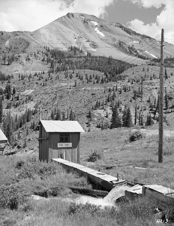 """16. """"View of a small, tar paper sided shed with a sign that reads: """"Fire Pump"""" at the Treasury Tunnel Mine in Ouray County, Colorado. Water rushes out of a wooden flume box on the ground."""" (1939)"""
