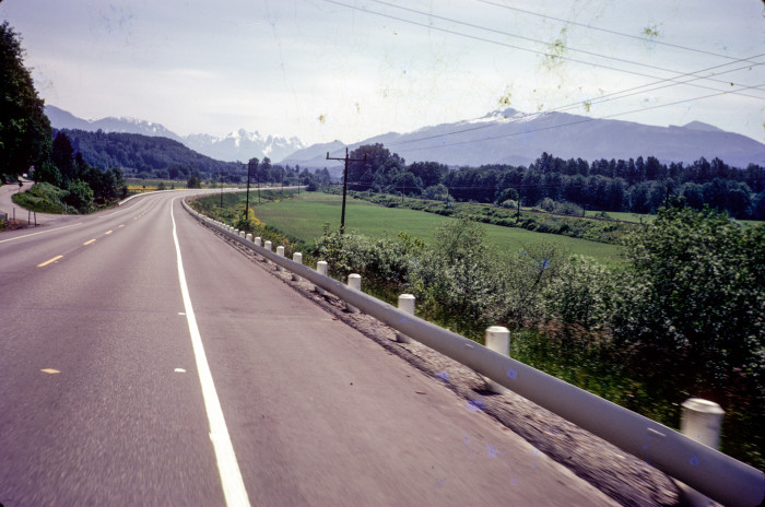 13. Driving along Highway 2 in 1974, with the Cascade mountains in the distance.