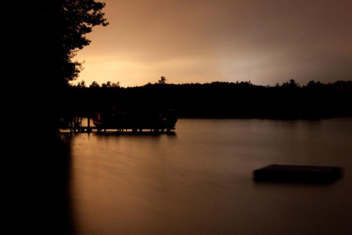 4. An orange sunset over a smooth lake.