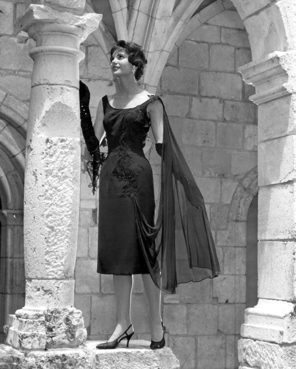 28. A fashion model in dress poses by column at Ancient Spanish Monastery: North Miami Beach, Florida, 1959
