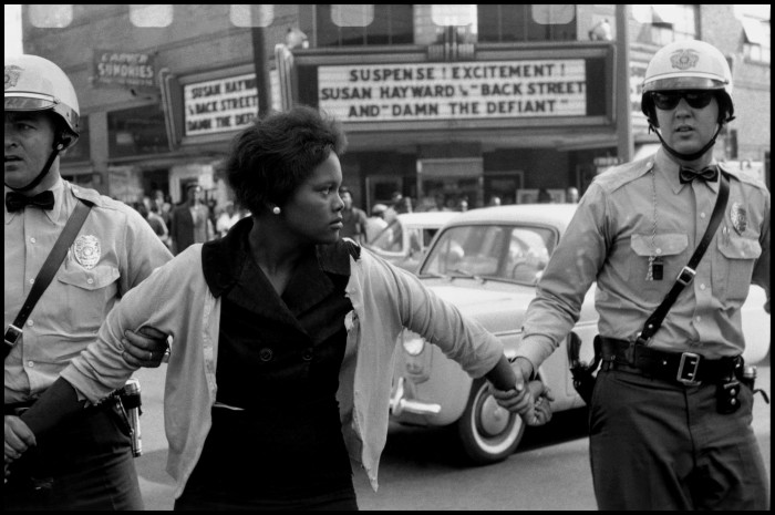 4. In 1963, a female protester in Birmingham, Alabama is being arrested and led away by the police.