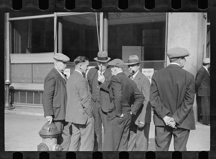 7. Men talk on a street corner in Manchester.