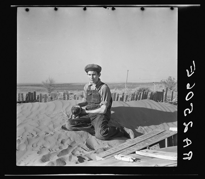 "5. ""A farmer's son playing on one of the large soil drifts which threaten to cover up his home. Liberal, Kansas."" (1936)"