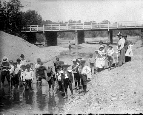 """12. """"A group of boys wade in the South Platte River as their teacher looks on from the bank, Denver, Colorado. The Alameda Avenue bridge is in the distance."""""""
