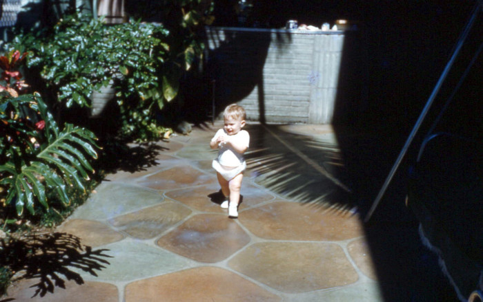 7) A young child hangs out on a Hawaiian patio in 1960.