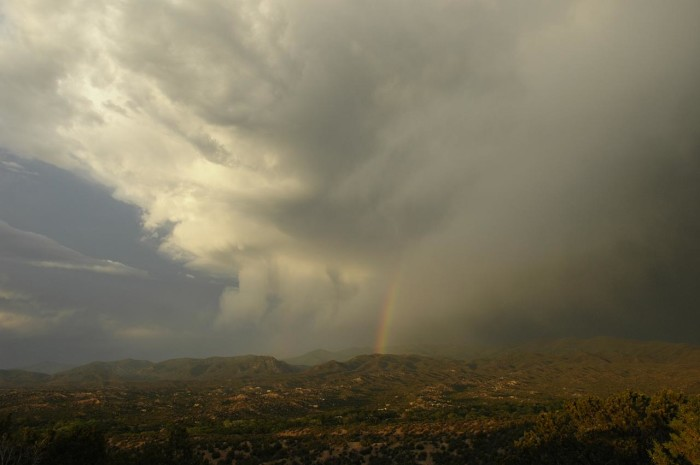 14. A rainbow battles the clouds to shine over Albuquerque.