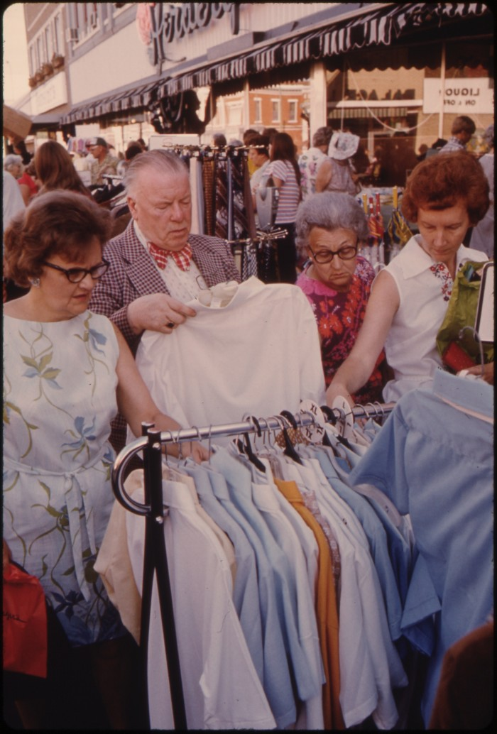 9. In New Ulm, adults are looking at the bargain merchandise set out for this massive sale.