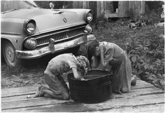8. Girls washing their hair in 1964. Likely this was in a poor part of Kentucky.