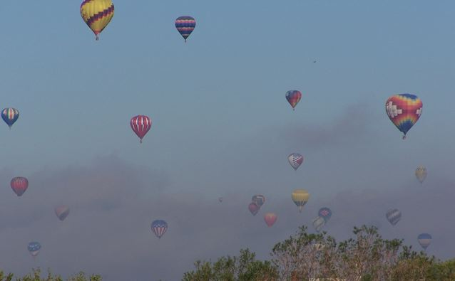 7. Hot air balloons participating in the Albuquerque Balloon Fiesta ascend through the fog.