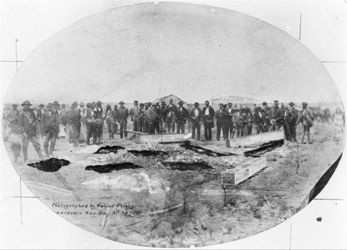 """""""A photograph showing a large group of men looking at the graves of those murdered  by the Bender family."""""""