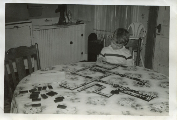 4. Here, Lloyd Earnest plays with dominos at a house near Cameron in the 1950s.