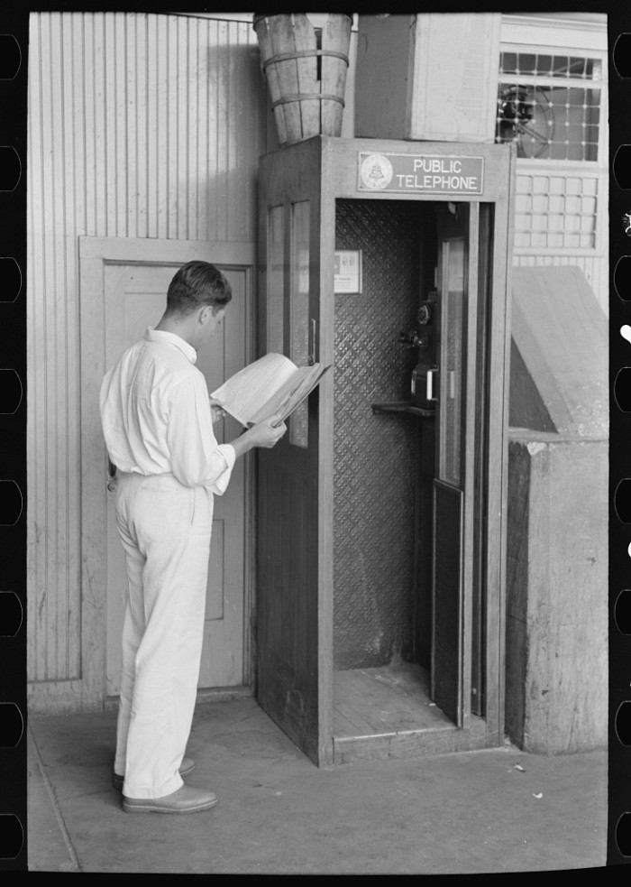 8. This nicely dressed gentleman is looking up a phone number before he makes a call in the phone booth. Taken in Oklahoma City in July 1939.