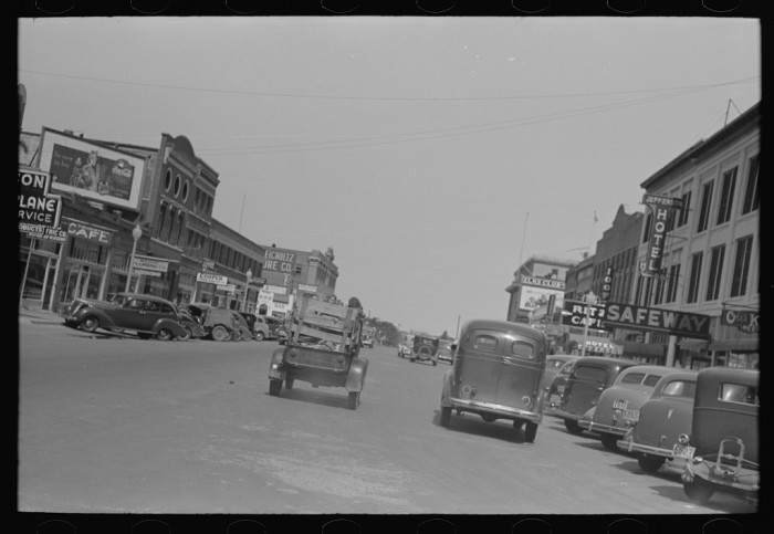 6. Main Street Muskogee with a migrant's car passing down the middle of it. Taken July 1939.