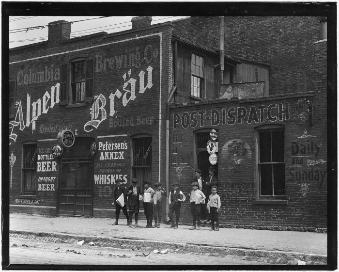 1.News boys standing in front Johnston's Branch and adjoining Saloon. St. Louis, May 1910.