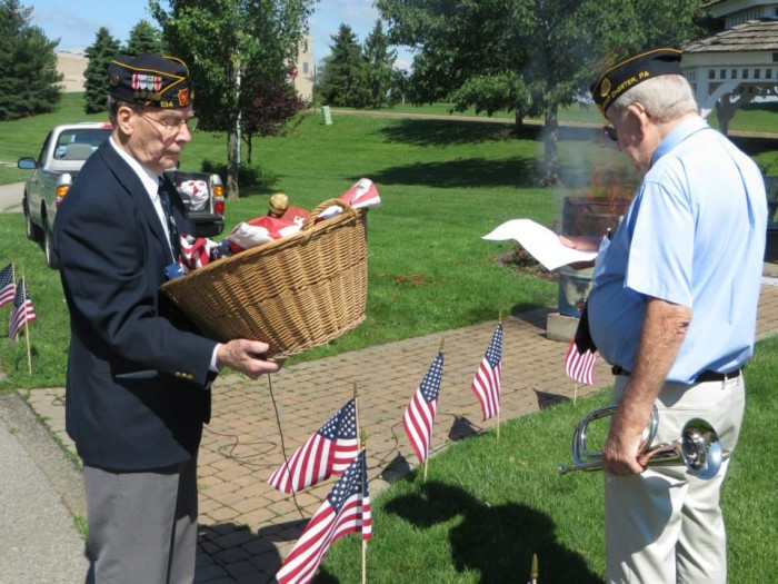 9. The residents of West Goshen know the meaning of patriotism; here, some members of the American Legion retire American flags at one of the local public parks.