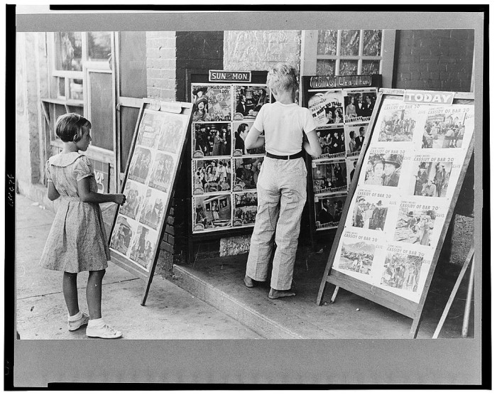 16.	Children looking at posters in front of a movie theater on a Saturday, Steele, August 1938.
