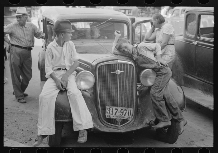 19.	Children sitting on the fenders of a car in Steele, August 1938.
