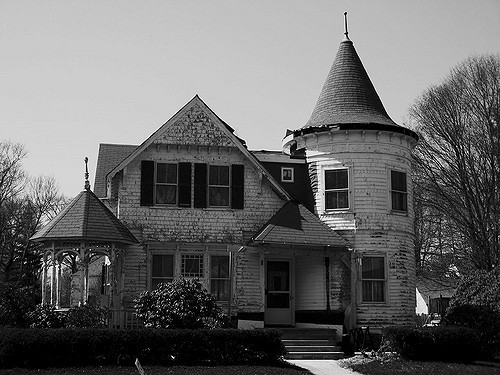 9. First of all, automatic points for having a giant witch's hat on top of a spooky tower. The photo looks grainy, possibly taken by a ghost. The house is in obvious disrepair and has a charming little round porch thing stuck to its side, which is a perfect spot for a pale, glowing woman in Victorian garb to stand and stare at kids riding by on hoverboards. Major points off for a well-maintained box henge. Ghosts hate crisp landscaping. 6/10.