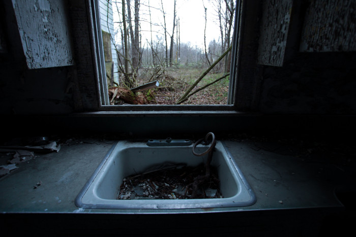 Even the sinks are filled with waste. The only light coming from broken windows...
