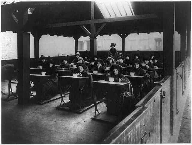 1. Children eating at their desks at an open-air school in Boston, dressed in heavy clothing. (1900)