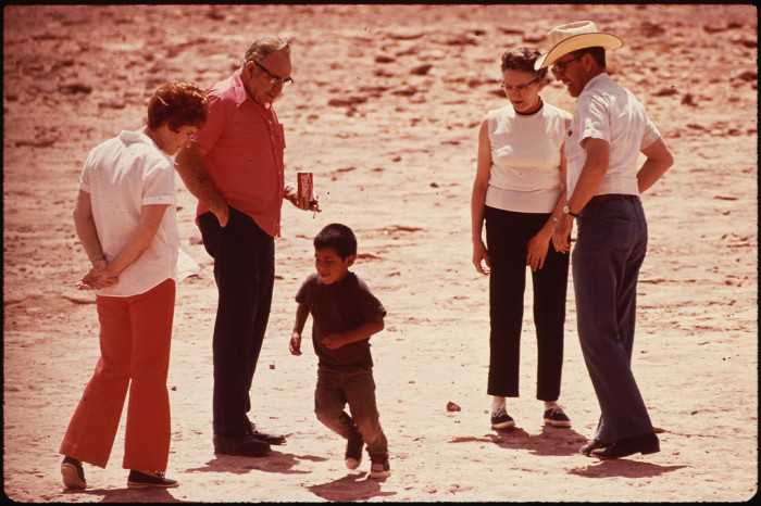 18. Tourists watch a little kid run around in 1972 on the Navajo Nation.