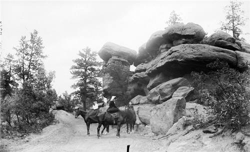 """7. """"View of three women on horses on a dirt roadway near rock formations at the Garden of the Gods in El Paso County."""""""