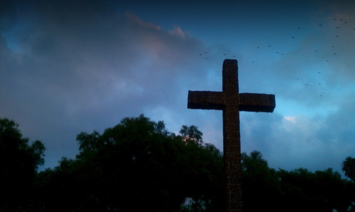 9. Birds fly in the night over a towering cross in Presidio Park in Old Town San Diego.