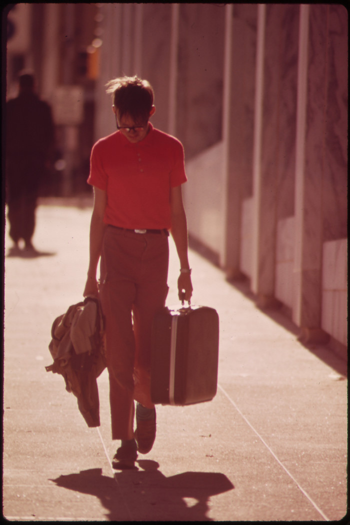 20. A rather dejected-looking your man walks down a street in downtown Omaha, suitcase in hand, May 1973.