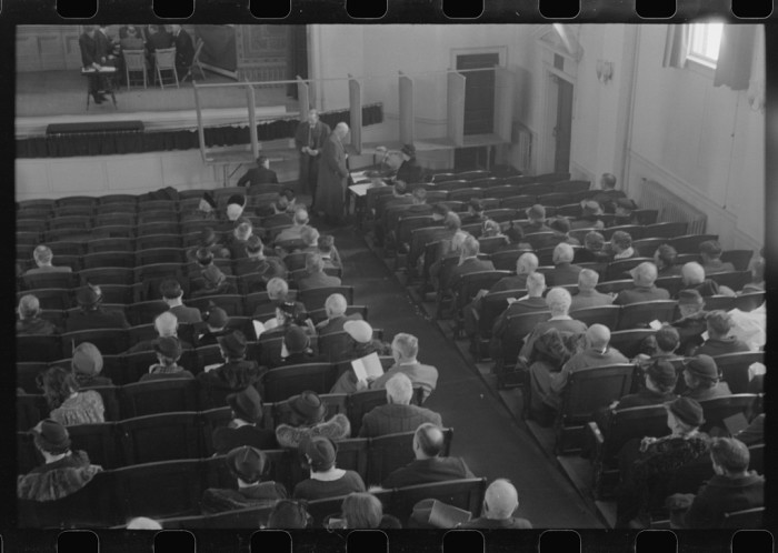 19.  Townspeople listening to discussion and balloting during a town meeting in Woodstock.