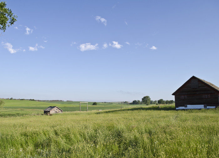 9. Wide, expansive prairies surround these farm buildings.