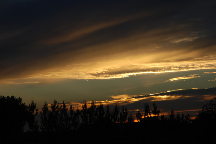8. The last rays of the sun, already disappeared behind the horizon, reflect golden light off these clouds against the dark night sky.