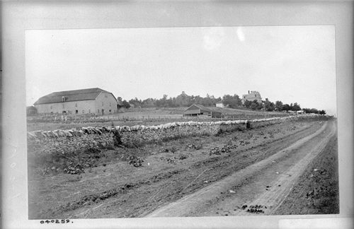 "2. ""A stone wall lines the dirt road that runs in front of what is identified as the Deer Park Farm in Strong City."""