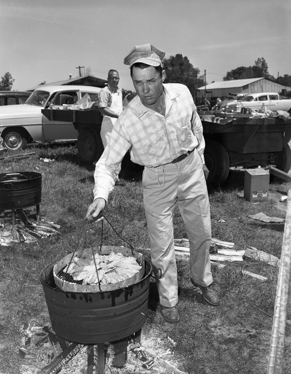 11. Unidentified man frying fish for the annual farm field day at Velda Dairy Farms