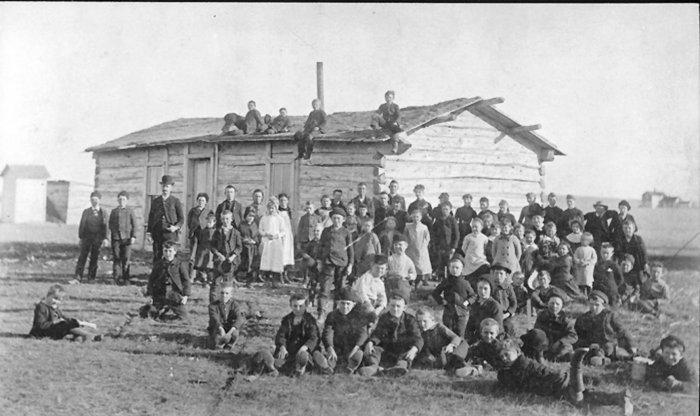 16. Rushville School - 1885. This old photo is quite the gem. It shows students gathered around and even atop the sod-roofed log schoolhouse.