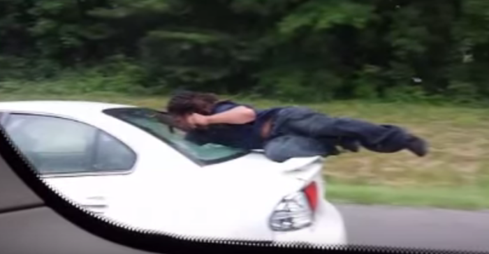 """5. """"Man Rides On Back Of Moving Car."""""""