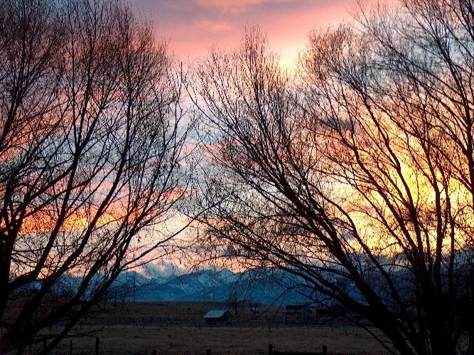 10. The sun sets over a Ravalli farm with the beautiful Bitterroot Mountains in the background.