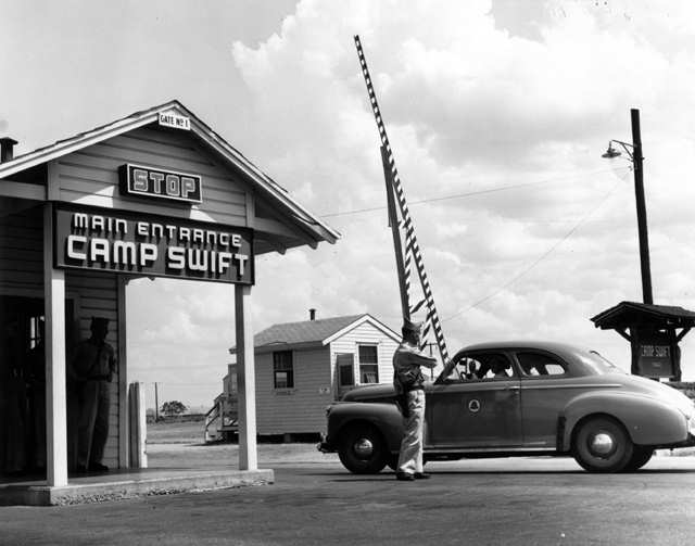 9. A military policeman allows a car to pass through the entrance to Camp Swift, an army training base in Bastrop County.
