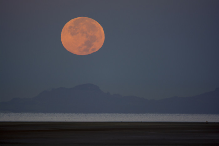 Before you head home, take one last look. The moon over the island is a thing of beauty.