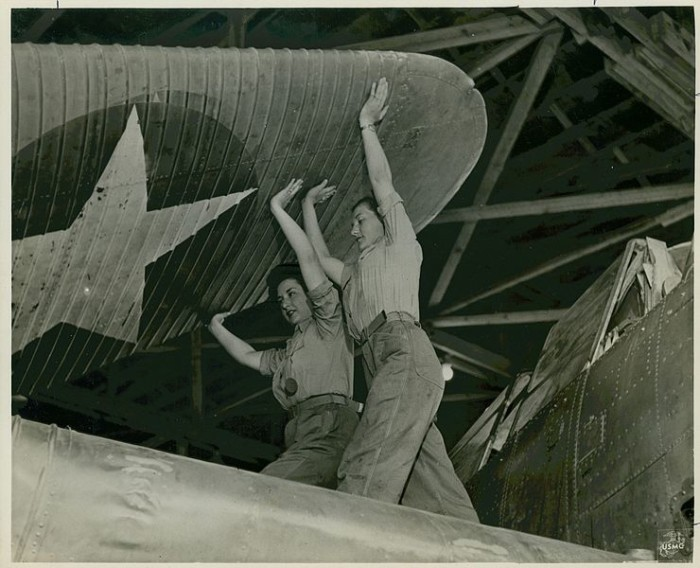 7. Two members of the Marine Corps Women's Reserve in training at the Naval Air Technical Training Center, Norman, Oklahoma. They are unfolding the wing section to flight position during a day's work at the school, 1943.