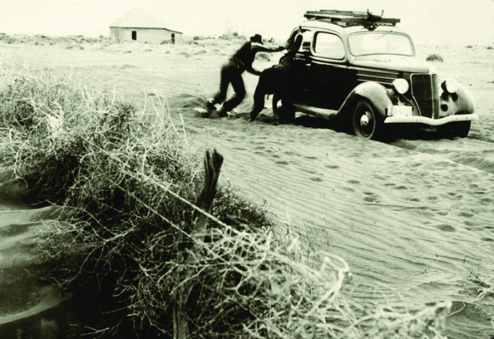 8. These men are trying to get their car to move through the dust accumulated on the road from wind erosion. The photo was taken about 8 miles southwest of Felt, Oklahoma, 1939.