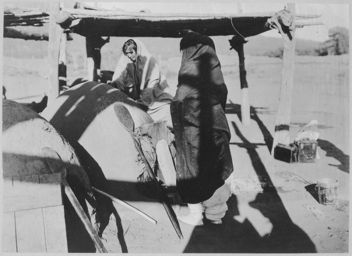 4. Two women baking bread in a horno (outdoor oven) in Taos, in 1916.