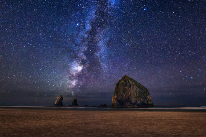 3. The Milky Way illuminates the night sky above Haystack Rock.