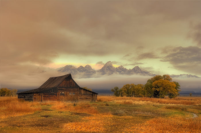 7. This looks like a portrait instead of a photograph of a cloudy sunrise over the Moulton Barn.