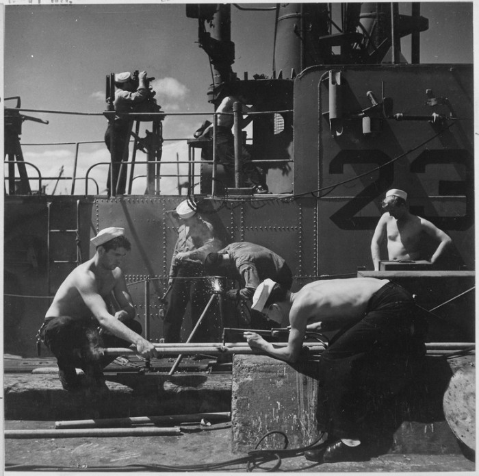 13. Servicemen at Pearl Harbor repair and check instruments aboard a submarine that has just returned from war in 1945.